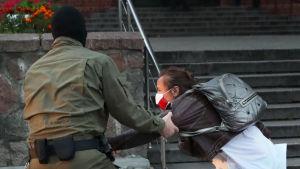 Naamioitunut mies kiskoo naismielenosoittajaa käsivarresta.