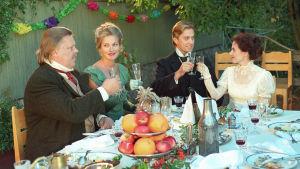 Kuvassa kaksi naista ja kaksi miestä, skoolaavat laseillaan toisen parin hääjuhlassa.