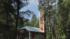 Varjakansaaren vanhan sahakylän paloasema, punavalkoinen rakennus jossa torni, metsän keskellä.