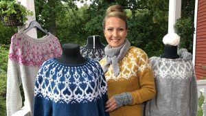 Lee Esselström står omgiven av stickade strömsötröjor i olika färger