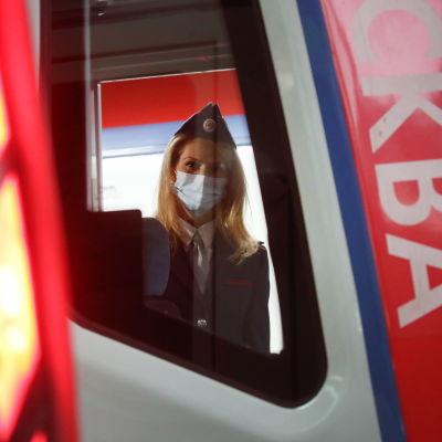 En kvinna i munskydd och uniform syns inne i loket på en metro i Moskva.