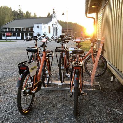 Fyra orange stadscyklar vid ett cykelställ.