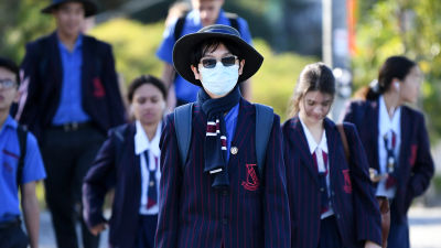Skolelever på väg till sin skola i Brisbane, Queensland på måndagen 11.5, deras första dag i skolan på flera veckor.