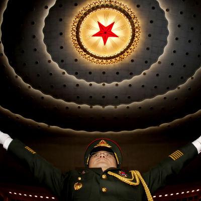 Dirigenten för ett militärband slår ut med händerna.