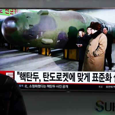 En sydkorean tittar på tv-nyheter i Seoul den 9 mars 2016. I nyhetssändningen figurerar Nordkoreas ledare Kim  JOng-un tillsammans med en missil.