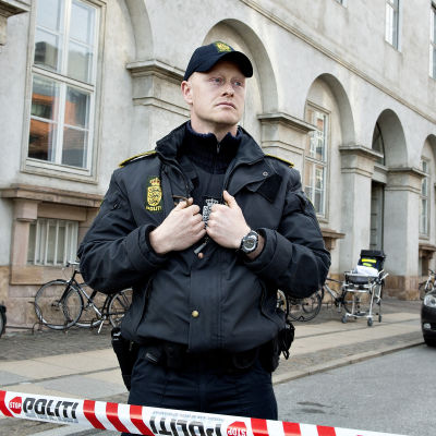 En ensam dansk polis står vid avspärrningsband på tom gata i Köpenhamn.