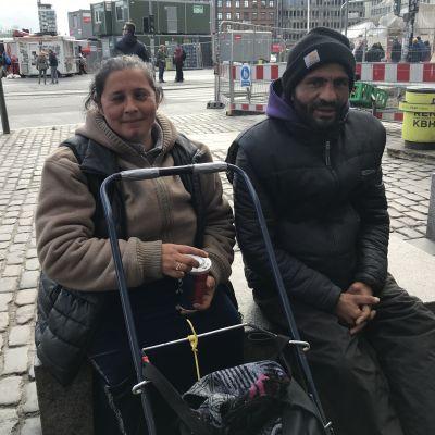 En man och en kvinna sitter på ett stenblock på ett torg i Köpenhamn.
