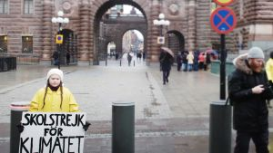 """På bilden syns klimataktivisten i ett regnigt Stockholm. Hon är klädd en gul regnjacka och håller i sin kända skylt """"Skolstrejk för klimatet""""."""