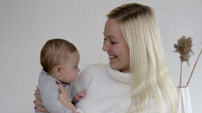 En kvinna med långt blont hår som håller en liten bebis i famnen. De tittar på varandra och hon ler.