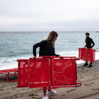 Työntekijät kantavat rantatuoleja uimarannalla.