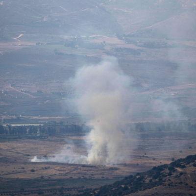 Rök stiger på ett fält efter artillerigranater slagit ned.