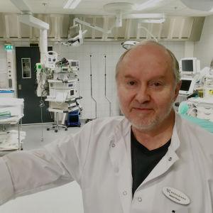 Sakari Orava står i dörröppningen till en operationssal i vit läkarrock.