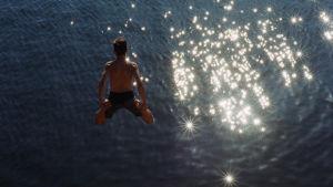 Ung kille hoppar ner i solglittrande hav.