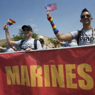 """Kaksi miestä marssii pride-kulkueessa ja heiluttaa Yhdysvaltain- ja sateenkaarilippua. He kantavat kylttiä, jossa lukee """"marines""""."""