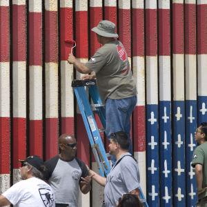 USA:s flagga målas upp och ned på en bit av muren mellan USA och Mexiko