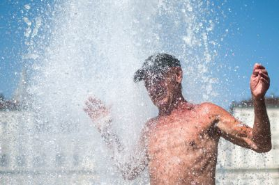 En man njuter av vattnet i värmen på Piazza Castello i Turin, Italien 12.8.2021