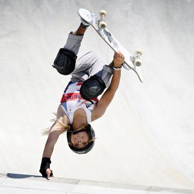Skateboardare i vit dräkt gör ett trick under sitt åk.