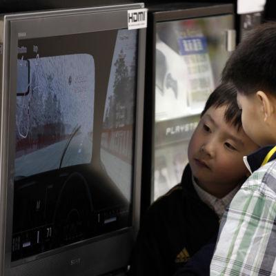 Ett par barn i Kina betraktar ett videospel på en skärm i en butik.