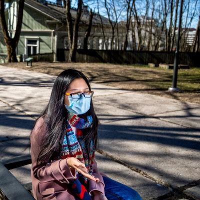 En mörkhårig kvinna med glasögon som har ett munskydd på sig.