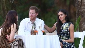 Mitt i bilden sitter prins Harry bakom ett bord med vinglas på, utomhus. Till höger om honom sitter Meghan Markle som håller en hand på hans axel. Mittemot dem, till vänster på bilden, sitter en kvinna med ryggen vänd mot kameran.