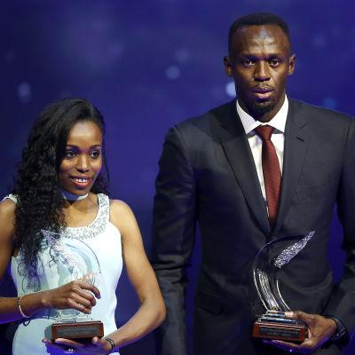 Almaz Ayana och Usain Bolt håller upp sina priser.