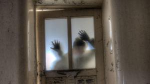 Miehen hahmo näkyy huuruisen ja vinon ovilasin läpi.