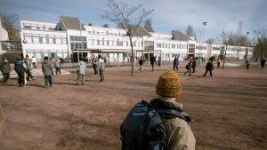 En pojke står ensam på skolgården och tittar på när andra barn leker.