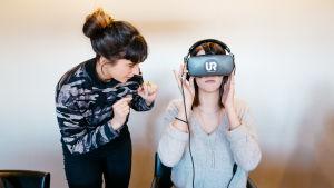 Saskia Oljelund näyttää UR:n tekemää koulukiusaamis-videoita, VR-silmikko päässä Jenna Karas