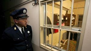 Japansk fängelsevakt ser på en sovande fånge.