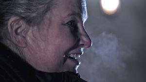 Hymyilevän naisen tiivis sivuprofiili, tumma kuva, öinen taivas ja kuu.