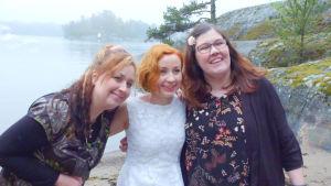 Kolme naista poseeraavat hymyillen kameralle taustallaan järvi- tai merimaisema kallioineen.