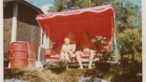 Helena Ahti-Hallberg alle 2-vuotiaana vanhempiensa kanssa aurinkoisella mökkipihalla puutarhakeinussa.