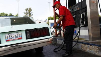 Arbetstagare vid servicestation tankar världens billigaste bensin