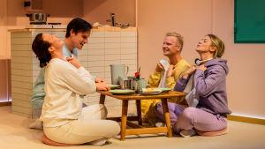 Fyra personer i pastellfärgade kläder sitter på golvet kring ett dukat bord.
