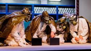Fyra gestalter i skyddsmundering och gasmasker sitter på golvet kring ett kassaskåp.