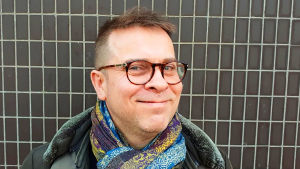 Muusikko Jukka Perko katsoo hymyillen kohti kameraa.