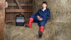 Kandi Emma istuu rennosti heinäladossa, vieressä eläinlääkärinsalkku