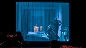 En mörk teaterscen. Bakom en halvgenomskinlig gardin syns stråkmusiker som sitter på en säng.