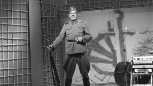 Einari Ketola esiintyy korpraali Möttösenä kivääri kädessä Iskelmäkarusellissa 1962.