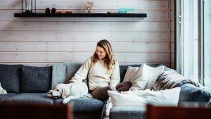 Nuori nainen istuu hirsihuvilassa kulmasohvalla ja silittää vieressään lepäävää koiraa.