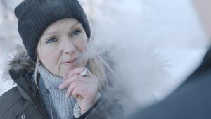 Anu Sinisalo i rollen som Lena Jaakkola i serien Sorjonen. Pipo och cigarrett i handen, snö bakom.