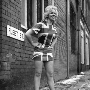 En kvinna poserar i en minikjol med Englandsflagga 1960-tal.