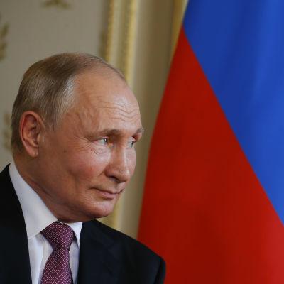 Vladimin Putin i profil framför den ryska flaggan under ett möte med Schweizs president Guy Parmelin (inte på bild).