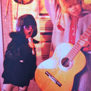 Muusikko Aili Ikonen pikkutyttönä laulamassa mikrofoniin karvalakki päässä.
