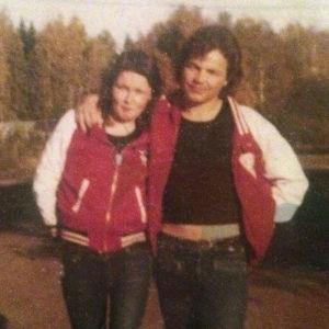 1970-luvun kuvassa nuoripari unisexasuissaan poseeraa kaulakkain kameralle.