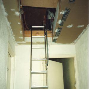 Rakennustikkaat, jotka johtavat porrastasanteelta remontoitavan sisäkaton keskellä olevaan vinttiluukkuun.