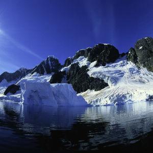 Nordpolen. I vattnet ligger ett stenigt berg som till hälften är täckt med tjocka lager is och snö. Himlen är blå och solen lyser klart.