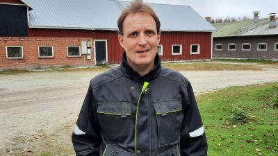 En man som står framför ett fähus.
