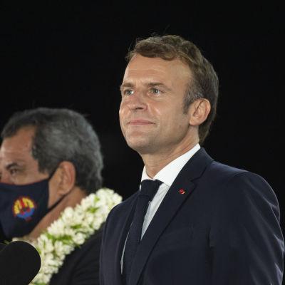 Bild på Frankrikes president Emmanuel Macron. Han står bredvid en person som applåderar, och en man i munskydd.