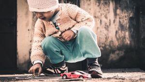 lapsi leikkii autolla pihalla